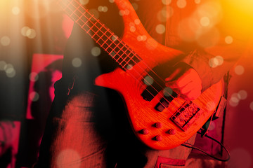 Life style image of close up young man hand, playing electric bass guitar
