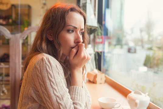 Nervous woman biting nails and looking away sitting alone in a coffee shop