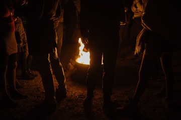 Silhouette of a group of people standing around a bonfire