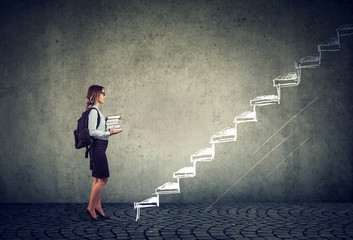 student with books standing on the stairs of education leading to success