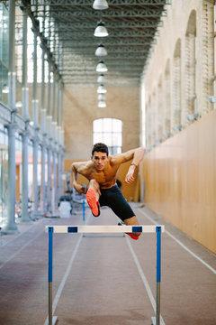 Shirtless sportsman jumping over bar