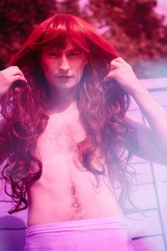 Non binary guy in drag wearing Merman style bare chest, red wig and white skirt