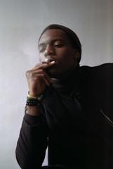 Stylish black man smoking with enjoyment