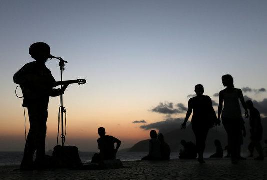 A man plays a guitar during a sunset on Arpoador beach in Rio de Janeiro