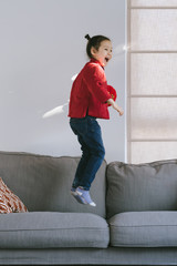 Lovely little girl in chinese custom holding a latern and jumping on sofa