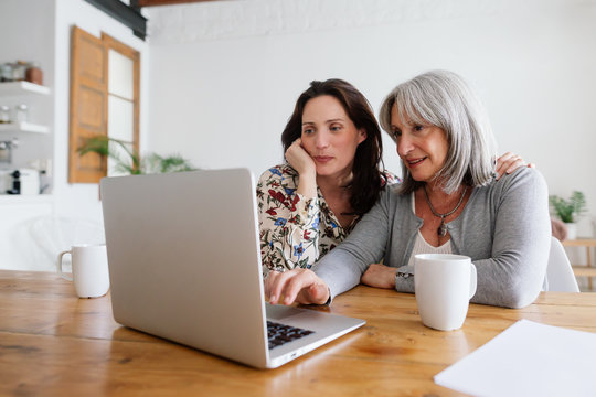 Mother and her daughter using laptop at home.