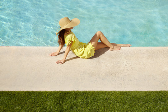 Side view of woman relaxing by poolside at resort