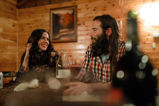 Two friends smile and talk together in a cabin in upstate New York