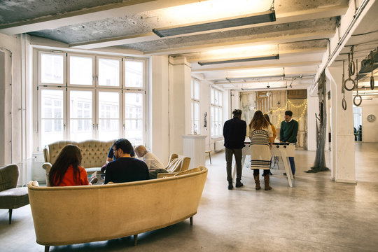 Group of Eight Young People Taking a Break in Bright Office Foye