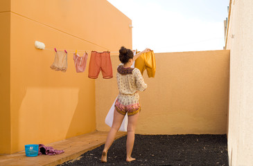 young woman hanging clothes on clothesline