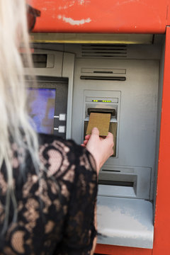 Woman inserting card in cash machine