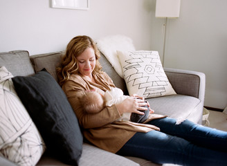 mom holds baby on couch
