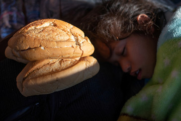 Girl, part of caravan of migrants from Central America, sleeps next to donated bread in Tapachula, Mexico
