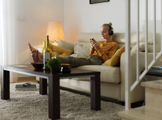Woman chilling at home with gadgets