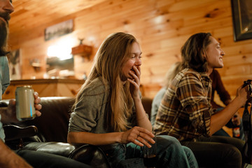 Young woman covers her mouth in laughter with a group of friends in cabin in upstate New York