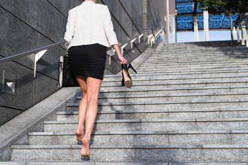 Businesswoman on the stairs without shoes