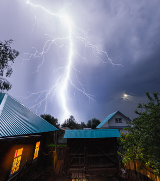 Thunderbolt in the night sky over the village with houses and garden