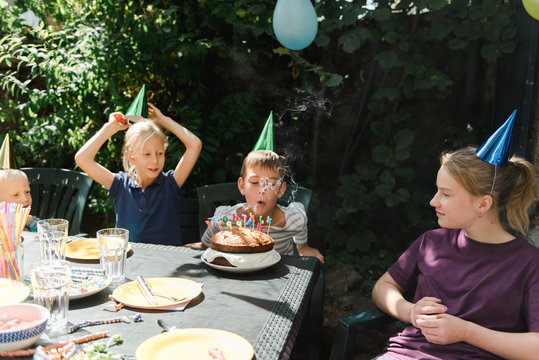 boy blowing out his candles on birthday cake