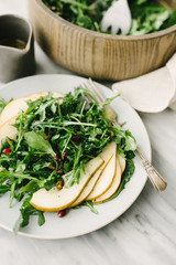 Angled view of pear and arugula salad with champagne vinaigrette