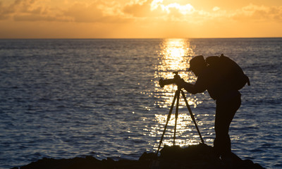 A photographer taking photos at sunset