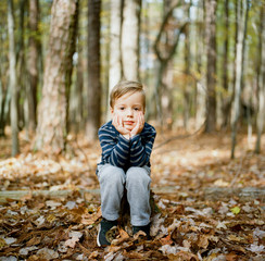 Adorable young boy sitting on a stump looking bored