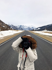a girl stands in the middle of the road in the winter and takes pictures with a film camera