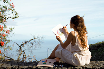 young woman making watercolor painting outdoors