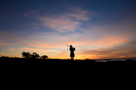 Bagpiper at sunset by the ocean