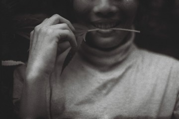 Black and white film photo of a young woman biting marijuana leaf