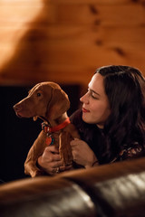 Young woman cuddles with puppy in a cabin upstate