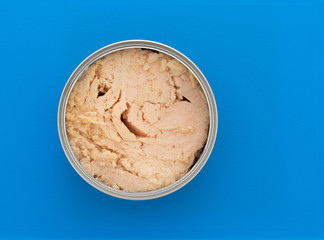 Top view of an opened can of solid white albacore tuna in olive oil atop a blue plastic cutting board.