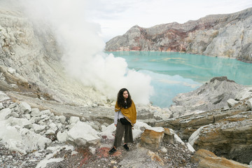 Young woman in respiratory mask standing on the hill in sulfur smoke on volcano road in Java.