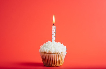 Birthday cupcake with polka dots candle on a red background