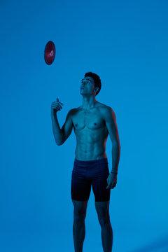 Athletic man throwing disk up in studio