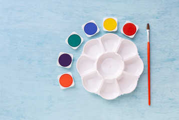 White watercolor palette with watercolor tablet with red brush on blue background, art and creation