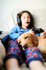 Girl with dog on sofa playing game