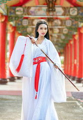 Beautiful Chinese woman with a traditional suit with a sharp sword in her hands, Beautiful and belligerent face, Young woman with a samurai bushido katana sword