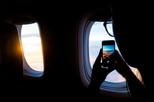 A young woman taking a picture out of an airplane window at sunset