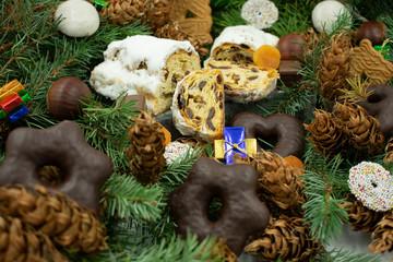 Bratapfel- und Butterstollen und verschiedene Weihnachtsleckereien auf Tannenzweigen.