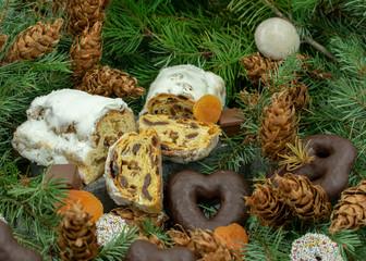 Weihnachtsstollen und verschiedene Weihnachtsleckereien auf Tannenzweigen.