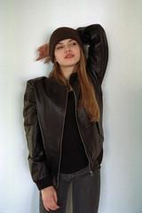 Stylish woman leaning on white wall