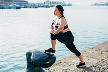 Plus size woman doing stretching exercises at seaside.