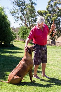 man feeding dog a large ham bone