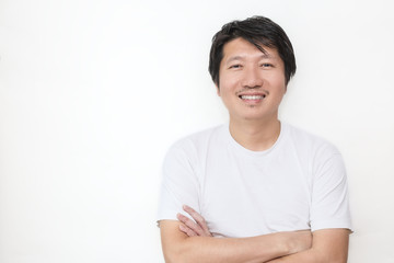 Attractive beautiful smiling positive asian happy man. Closeup portrait asian polite man wearing t-shirt with crossed arms isolated on white background.