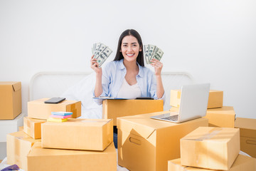 Startup SME freelance woman holding money working at home office , Young Asian small business owner using computer, online marketing packing box delivery, SME e-commerce telemarket concept