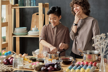 Cheerfully women dyeing Easter eggs