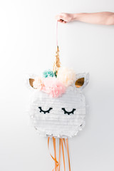 cute pastel paper party unicorn pinatas behind a white wall