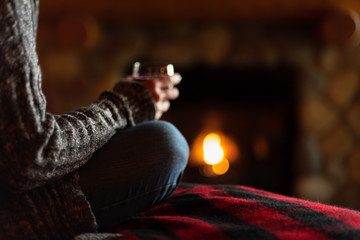sitting in cozy cabin by fieldstone fireplace with glass of wine