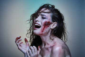 Beautiful girl with a wounded face in the blood