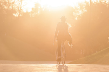 Male's silhouette riding vintage bicycle in the golden hour